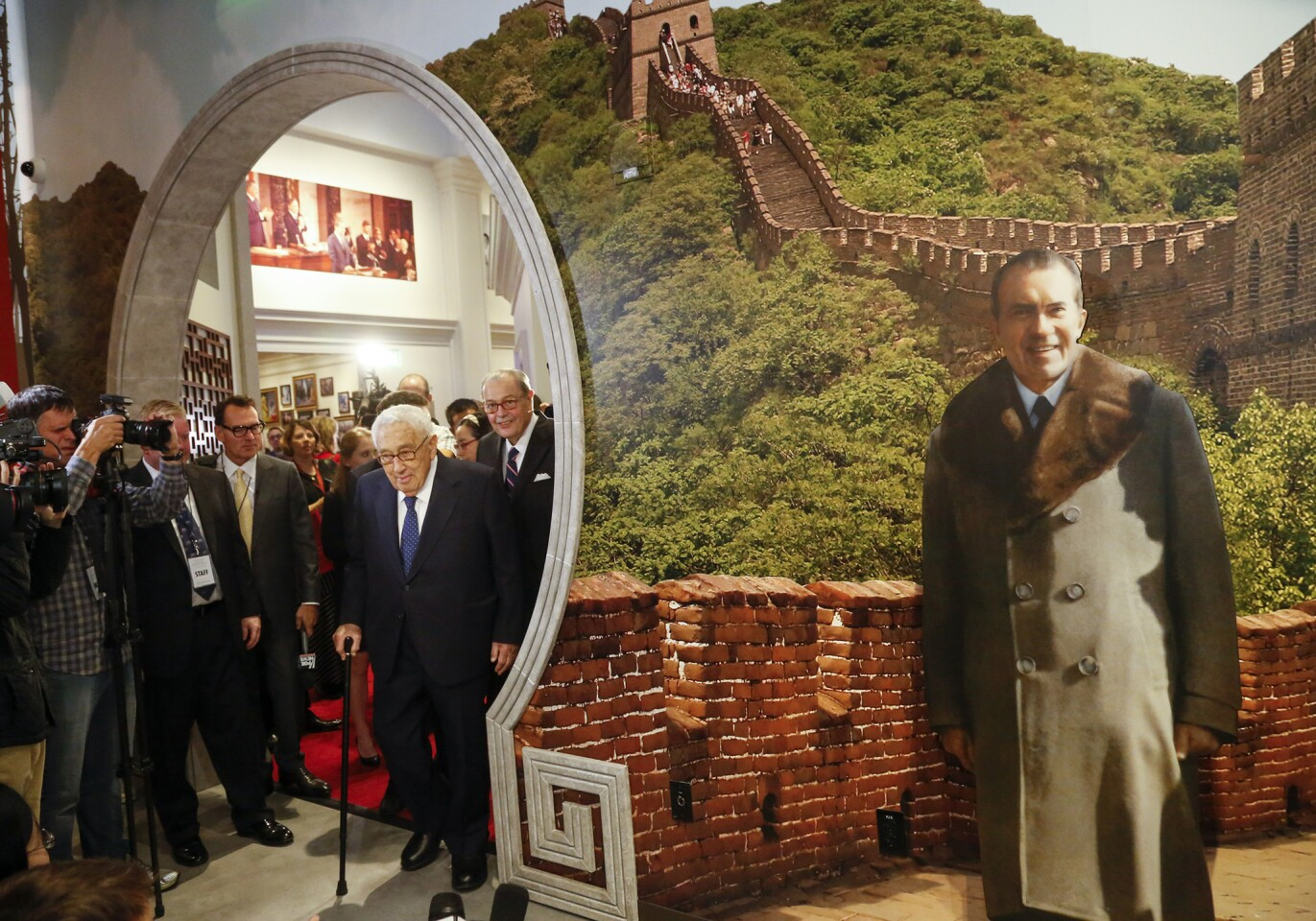 Former Secretary of State Henry Kissinger enters an exhibit in the Richard Nixon Presidential Library and Museum in Yorba Linda where guests can pose with a life-size backdrop of Nixon in front of the Great Wall of China.