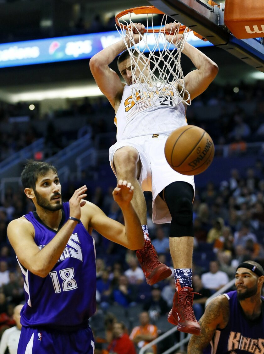 Phoenix Suns' Alex Len (21) dunks over Sacramento Kings' Omri Casspi, of Israel, during the second half of an NBA basketball game, Wednesday, Nov. 4, 2015, in Phoenix. (AP Photo/Matt York)