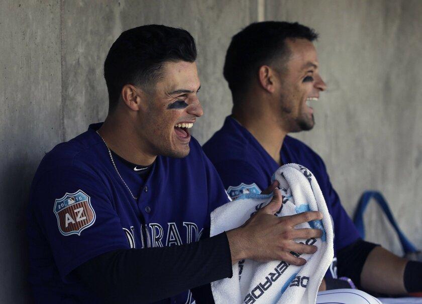 Colorado Rockies' Nolan Arenado, left, and Gerardo Parra laugh in the dugout during the second inning of a spring training baseball game against the Arizona Diamondbacks in Scottsdale, Ariz., Thursday, March 31, 2016. (AP Photo/Jeff Chiu)