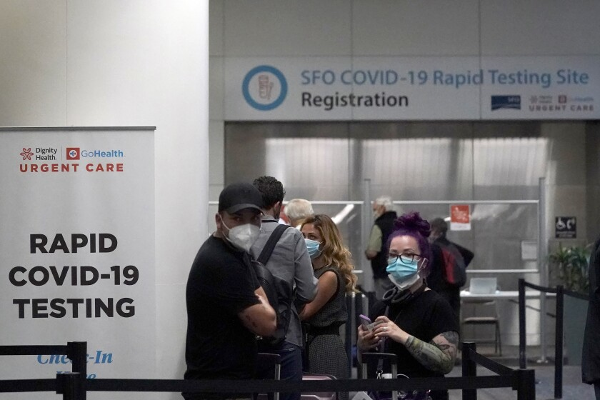 United Airlines passengers wait to register at the COVID-19 rapid testing site at San Francisco International Airport
