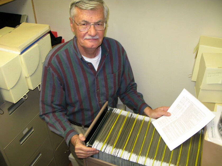 Art Goddard works with photographic negatives in the archives of the Costa Mesa Historical Society.
