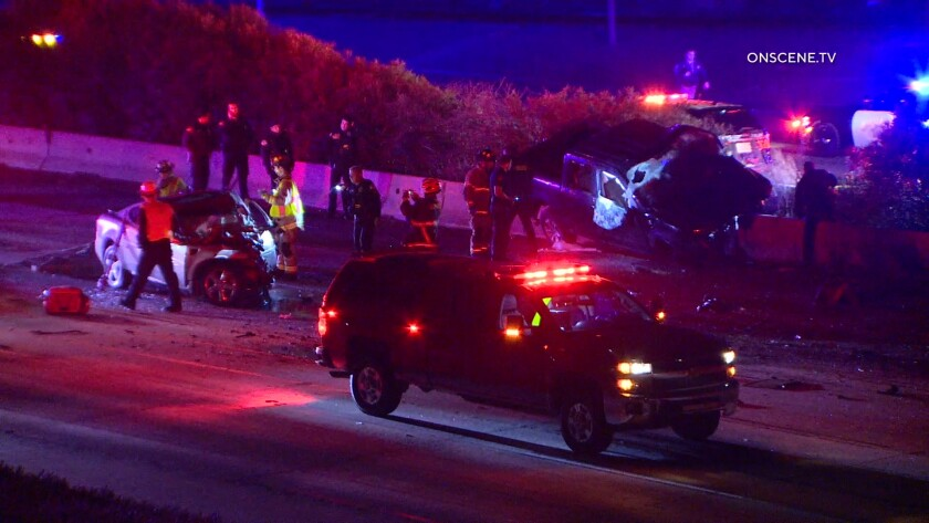 Firefighters, the CHP and police work on Interstate 5 where the drivers of the pickup and the sedan died in a collision early Tuesday. The pickup was headed south on Interstate 5 in northbound lanes. Oceanside police had pursued the pickup driver moments earlier for a traffic violation.