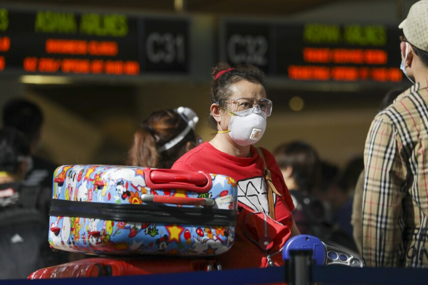 An LAX passenger, mask in place, lines up on May 22.
