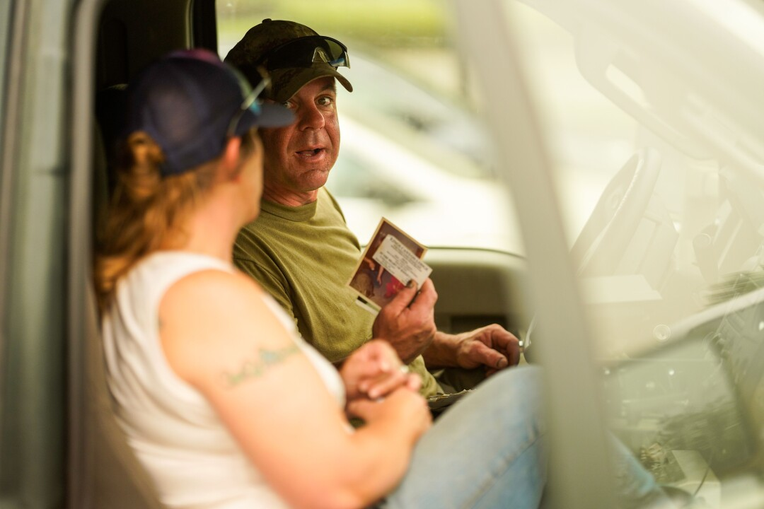 Niles and Gabrielle Kant look at photos in the cab of their truck.