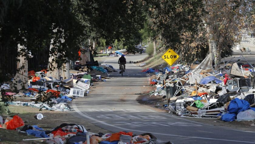 A cyclist passes trash from the Santa Ana River homeless camp in Anaheim in February after it was cleared and more than 700 people relocated.