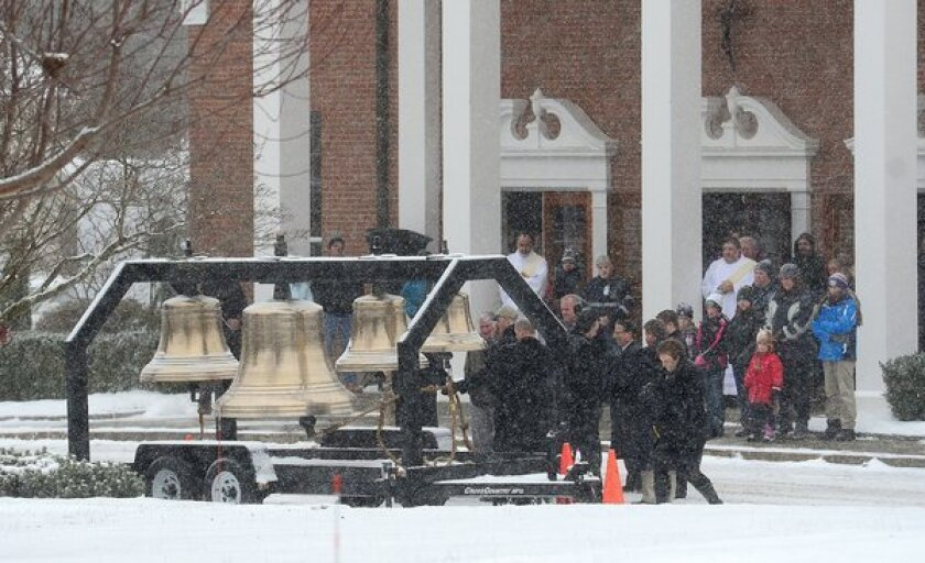 Residents gather outside St. Rose of Lima church as bells ring 26 times and the names of the Sandy Hook Elementary School shooting victims are called over a loudspeaker in Newtown, Conn., on Saturday.
