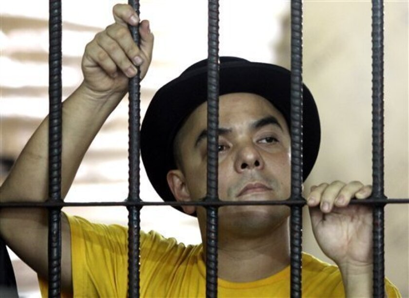 Carlos Celdran holds on prison bars inside the detention cell Friday, Oct. 1, 2010 in Manila, Philippines. Celdran was arrested after he disrupted a mass in protest to the church opposition to the promotion of artificial birth control methods. (AP Photo/Pat Roque)