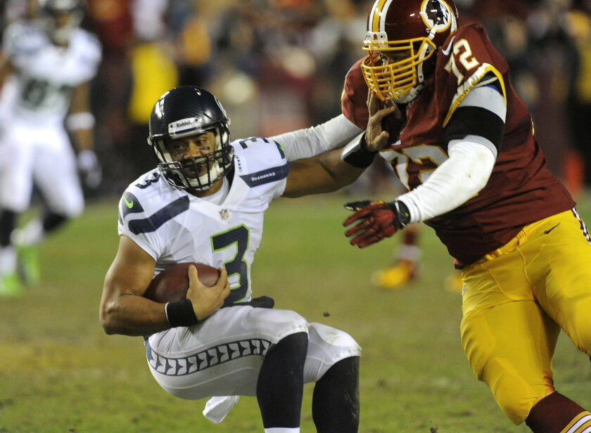 In this photo taken Jan. 6, 2012, Redskins defensive endStephen Bowen (72)  tackles Seahawks quarterback Russell Wilson during their NFL playoff football game in Landover, Md. Bowen has retired after playing 10 NFL seasons with Dallas, Washington and New York Jets. (AP Photo/Richard Lipski)