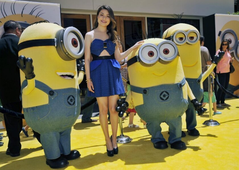 """Miranda Cosgrove poses with minion characters at the premiere of """"Despicable Me 2."""""""