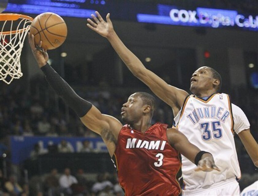 Miami Heat guard Dwyane Wade, left, goes up for a shot in front of Oklahoma City Thunder guard Kevin Durant, right, in the first quarter of an NBA basketball game in Oklahoma City, Sunday, Jan. 18, 2009. (AP Photo/Sue Ogrocki)