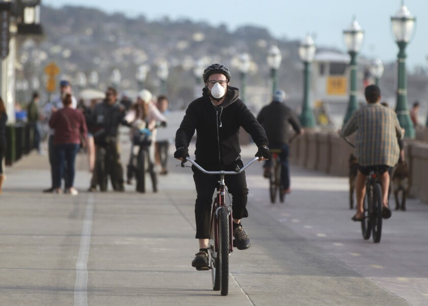 A Mission Hills resident wears a mask as he rides his bike on Mission Beach Boardwalk.