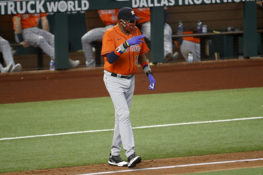 Houston Astros manager Dusty Baker Jr. signals as he walks to the mound to change pitchers during the fourth inning of a baseball game against the Texas Rangers in Arlington, Texas, Sunday, Sept. 27, 2020. (AP Photo/Roger Steinman)