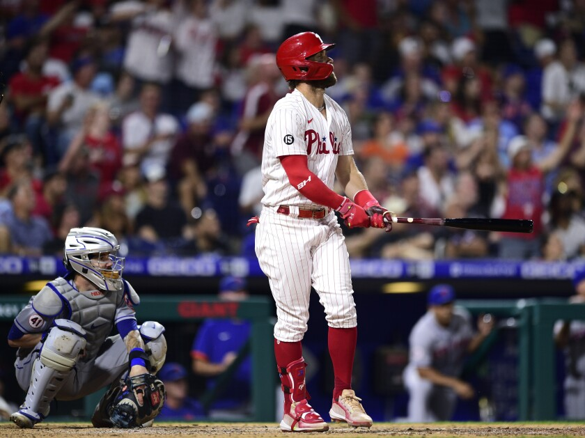Philadelphia Phillies' Bryce Harper, right, watches his two-run home run off New York Mets' Yennsy Diaz during the eighth inning of a baseball game, Friday, Aug. 6, 2021, in Philadelphia. (AP Photo/Derik Hamilton)