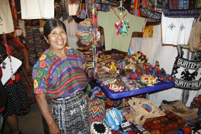 Migrante guatemalteca luce su traje regional al momento de vender sus productos en la Feria Chapina