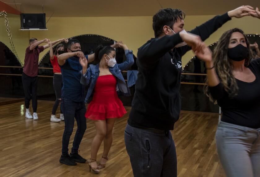 Six people in masks partner-dance inside an L.A. studio.
