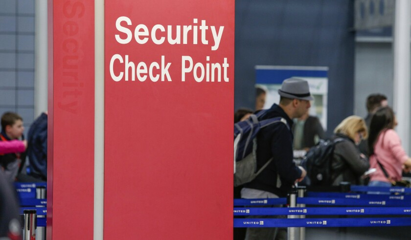 "FILE - In this March 22, 2016 file photo, passengers check into their flights near a security checkpoint sign at O'Hare International Airport in Chicago. The arrest of an airline mechanic suspected of being sympathetic with terrorists and charged with sabotaging a jetliner has renewed fear about the ""insider threat"" to aviation security. Despite security upgrades since the hijacking terror attacks of 2001, breaches including a gun-running operation at the nation's biggest airport illustrate the possibility that a well-placed airline or airport employee could bring down a plane. (AP Photo/Teresa Crawford, File)"