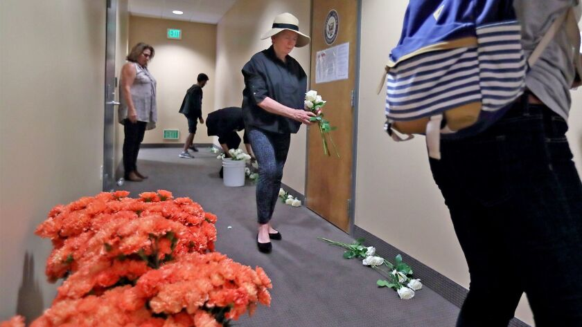 Constituents from California's 48th Congressional district lay out 58 white roses in front of Rep. D