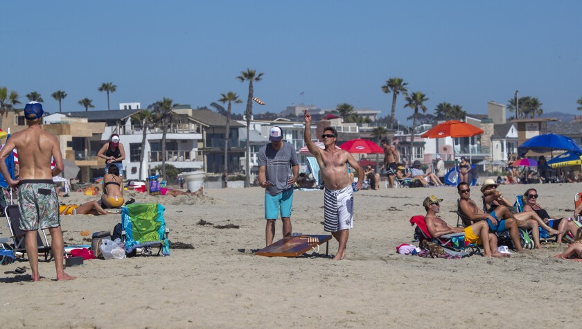 People play games and enjoy the sand in Newport Beach.