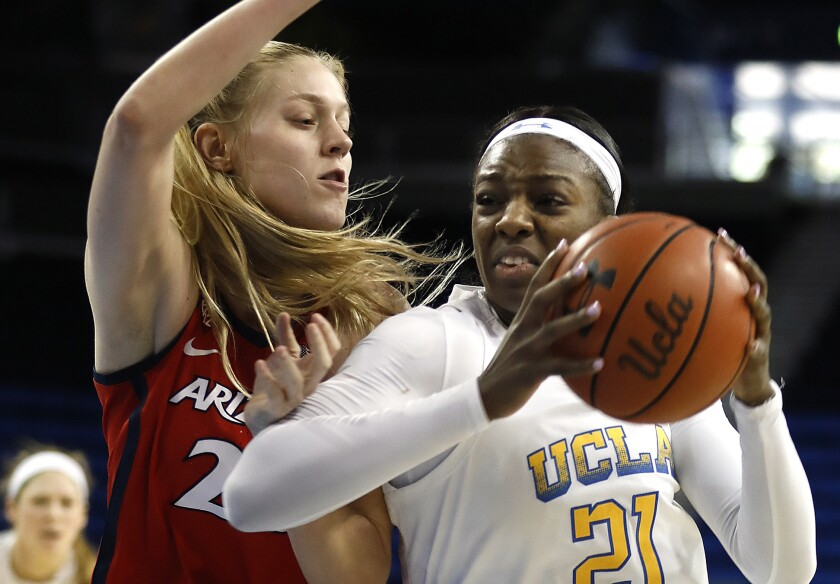 UCLA's Michaela Onyenwere, right, drives to the basket in front of Arizona's Cate Reese during the Bruins' win Sunday.