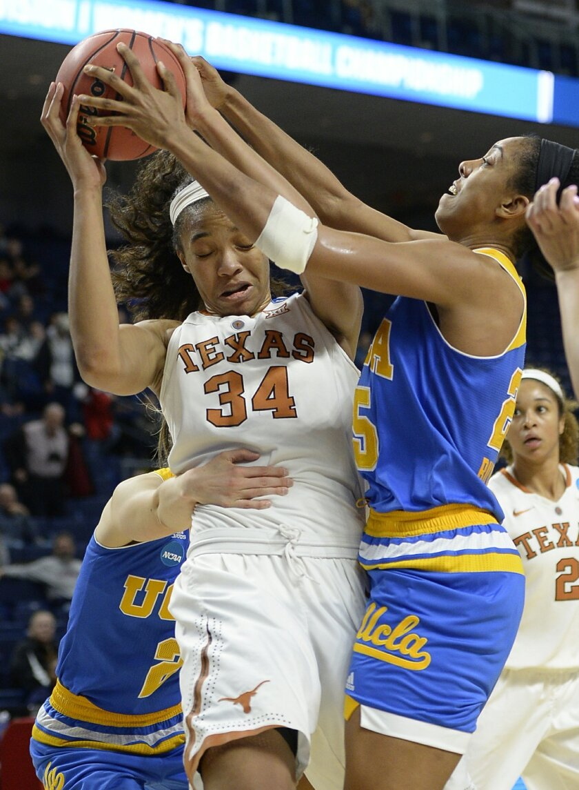 Texas' Imani Boyette, center, grabs a rebound against UCLA's Kari Korver, left, and UCLA's Monique Billings, right, during the second half of an NCAA college basketball game in the regional semifinals of the women's NCAA Tournament, Saturday, March 26, 2016, in Bridgeport, Conn. Texas won 72-64. (AP Photo/Jessica Hill)
