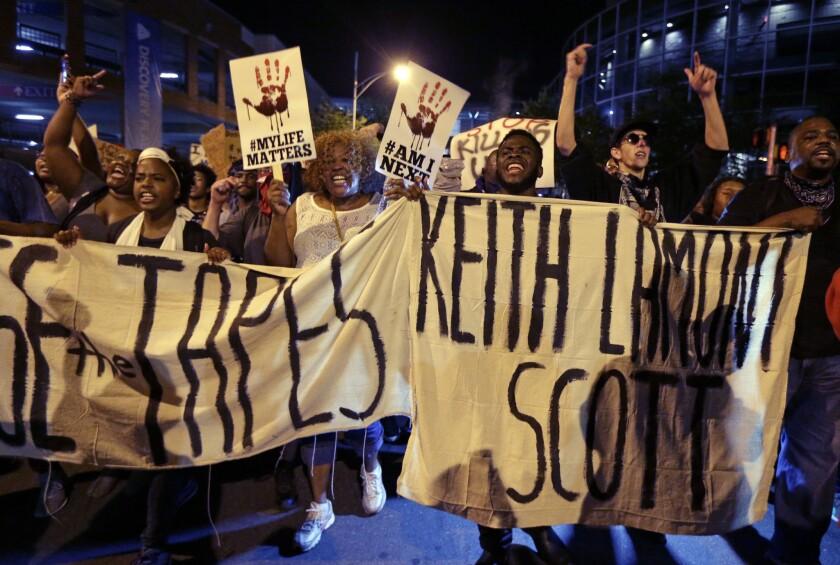 Manifestantes gritan mientras marchan en las calles de Charlotte, North Carolina, para protestar por la muerte a manos de un policía de Keith Lamont Scott. (AP Foto/Chuck Burton)