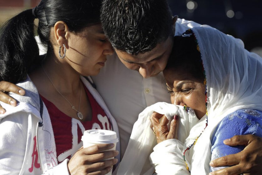 Amardeep Kaleka, son of the president of the Sikh Temple of Wisconsin, center, comforts members of the temple in Oak Creek, Wis. in August 2012. Twelve months ago, a white supremacist walked into a the temple and opened fire on worshipers he didn't know, killing six and devastating a Sikh community.