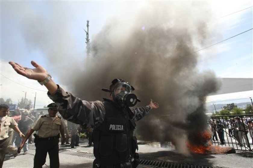 A police officer demonstrates next to a bonfire during a protest of police officers and soldiers against a new law that cuts their benefits at a police base in Quito, Ecuador, Thursday, Sept. 30, 2010. Hundreds of police protesting the new law plunged the country into chaos on Thursday, shutting do