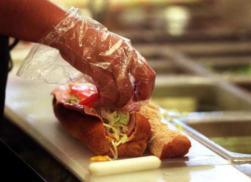 A Subway employee makes a sandwich. The chain was ranked one of the top five companies for best customer experience.