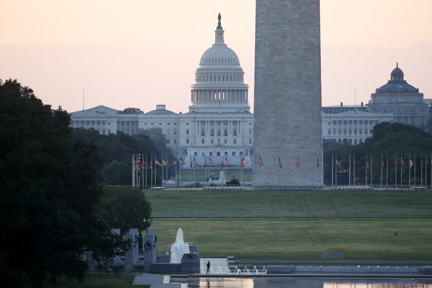 With the U.S. Capitol and Washington Monument in the distance, a man stands at the edge of the Lincoln Memorial Reflecting Pool at sunrise, Sunday, June 7, 2020, in Washington, the morning after massive protests over the death of George Floyd, who died after being restrained by Minneapolis police officers. (AP Photo/Patrick Semansky)