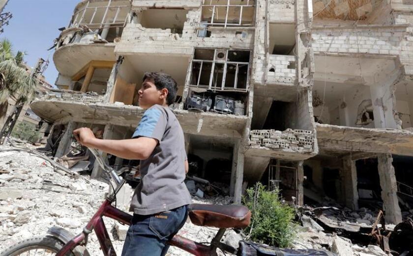 Un niño monta en bicicleta junto a un edificio en ruinas en la localidad de Duma, en Siria, el 20 de abril de 2018. Los expertos de la Organización para la Prohibición de las Armas Químicas (OPAQ) no lograron entrar el día 19 a la localidad de Duma para investigar el presunto ataque químico y siguen estancados en Damasco ante la falta de garantías de seguridad por parte de Siria y Rusia. EFE/Archivo