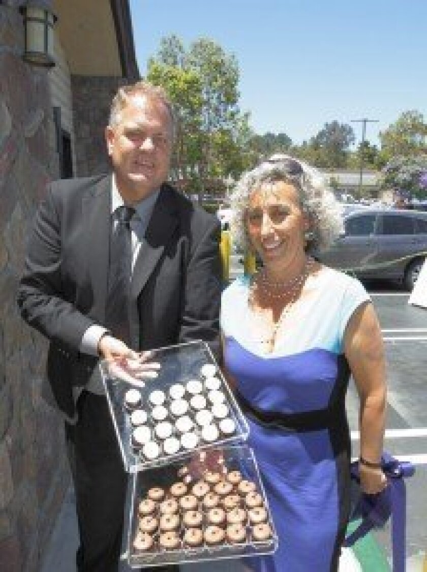Store manager Matthew Austin and owner Diana Benedek display their gluten- and corn syrup-free cupcakes.