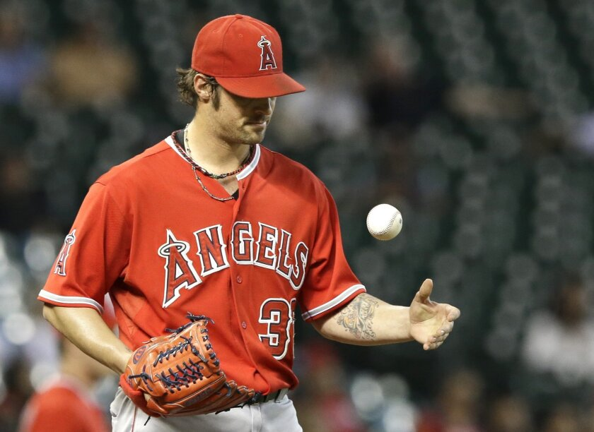 Los Angeles Angels starting pitcher C.J. Wilson tosses up the ball after giving up hits to the first two Houston Astros batters in the first inning of a baseball game Tuesday, Sept. 2, 2014, in Houston. (AP Photo/Pat Sullivan)