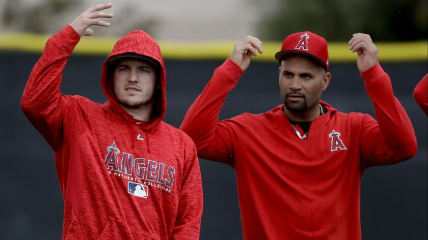Los Angeles Angels outfielder Mike Trout, left, and Albert Pujols arrive for practice at their sprin