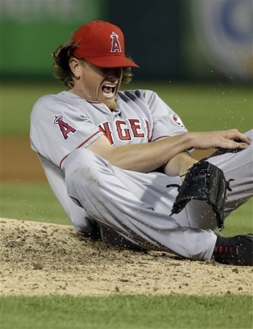 CORRECTS CONTEXT OF REACTION, PITCHER WAS NOT HIT - Los Angeles Angels starting pitcher Jered Weaver reacts after dodging a line drive and falling during the sixth inning of a baseball game against the Texas Rangers, Sunday, April 7, 2013, in Arlington, Texas. Weaver left the game. (AP Photo/LM Ote