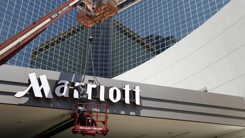 FILE - In this Tuesday, April 30, 2013, file photo, a man works on a new Marriott sign in front of t