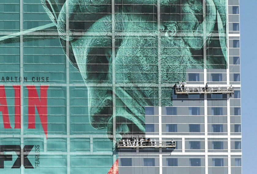 """Workers on suspended scaffolding complete installation of a giant mural for the FX Networks' """"The Strain"""" on the front of the Hilton San Diego Bayfront."""