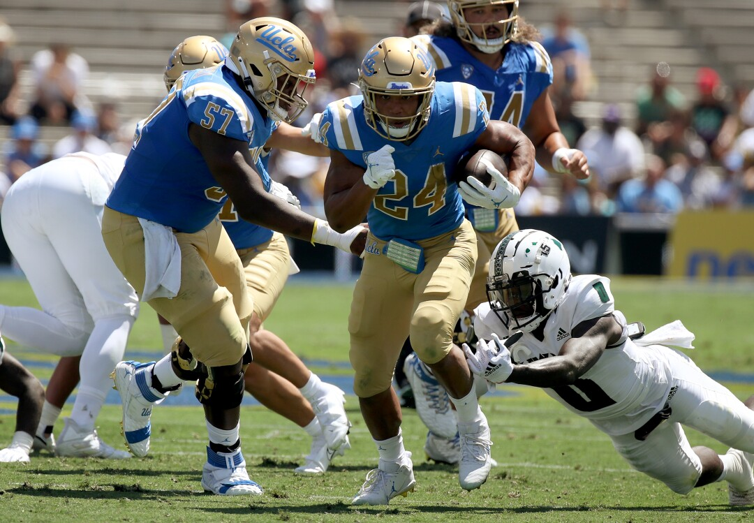 UCLA running back Zach Charbonnet breaks free for a touchdown run against Hawaii in the first quarter.