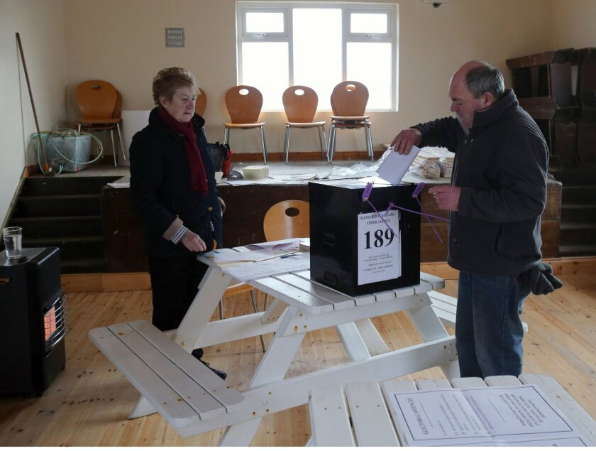 Presiding Officer Carmel McBride looks on as a resident casts his ballot as voting gets underway on the island of Inishbofin Ireland. People living on the remote isle of Inishbofin off the coast of Donegal are among the first to cast their ballots in Ireland's General Election, a day ahead of the rest of the country. (Niall Carson/PA Via AP) UNITED KINGDOM OUT