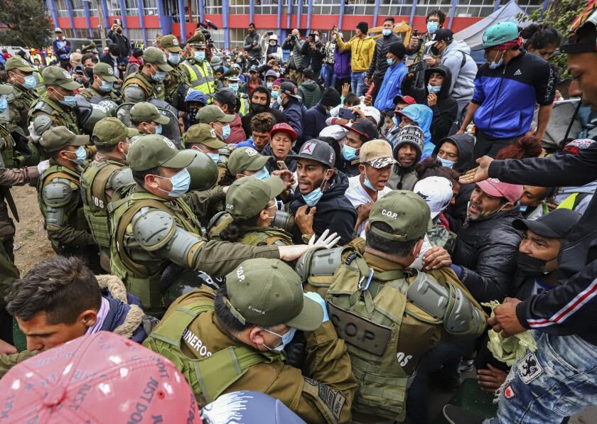 La policía chilena desaloja a migrantes venezolanos y colombianos de la Plaza Brasil donde viven en tiendas de campaña en Iquique, Chile, el viernes 24 de septiembre de 2021. (AP Foto/Ignacio Muñoz)