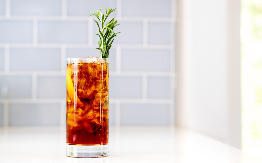 A tall glass is filled with ice and a brown beverage and a sprig of rosemary