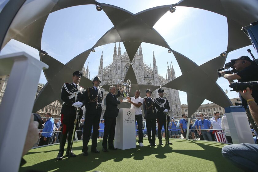 Milan's Mayor Giuliano Pisapia, third from left, and Brazilian soccer player Cafu, hold the Champions League trophy in front of the Duomo gothic cathedral, during the presentation of the Champions Festival event, in Milan, Italy, Thursday, May 26, 2016. The Champions League soccer final between Rea