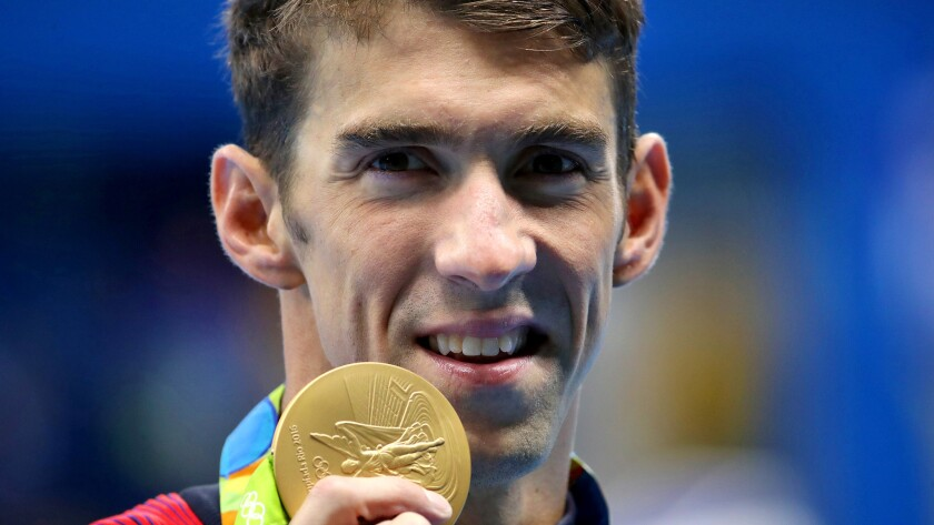 Michael Phelps shows off his fourth gold medal of the Rio Olympics on Thursday night after winning the 200-meter individual medley.