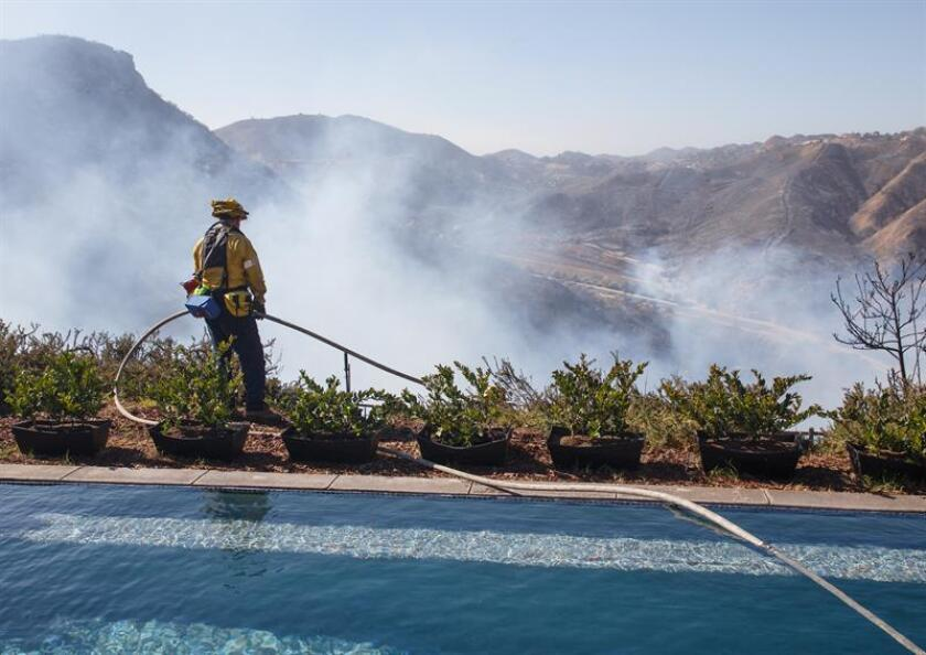 A firefighter looks out from the swimming pool in the backyard of a saved home after extinguishing a flare-up of the Woolsey Fire in West Hills, California, USA, 11 November 2018. The Southern California wildfire started on 08 November. EPA-EFE/EUGENE GARCIA