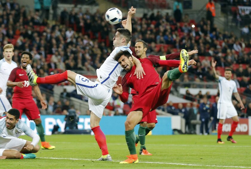England's Gary Cahill, left, and Portugal's Andre Gomes challenge for the ball during the International friendly soccer match between England and Portugal at Wembley stadium in London, England, Thursday, June 2, 2016 . (AP Photo/Frank Augstein)