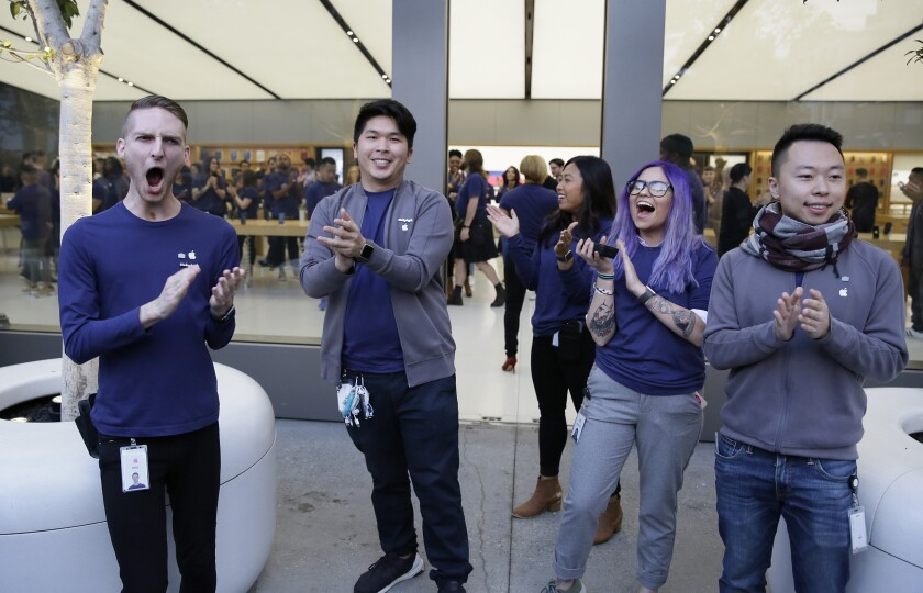 FILE - In this Nov. 3, 2017 file photo Apple employees greet customers as they wait to enter the Apple Union Square store in San Francisco. Employees at Apple stores must be paid for time they spend waiting for managers or security guards to search their bags to make sure they're not stealing anything, the California Supreme Court ruled Thursday, Feb. 13, 2020. (AP Photo/Eric Risberg,File)