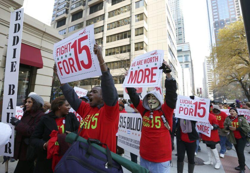 Un grupo de trabajadores de comercios minoristas, restaurantes de comida rápida y tiendas marchan en la avenida Michigan, la principal vía comercial de Chicago.