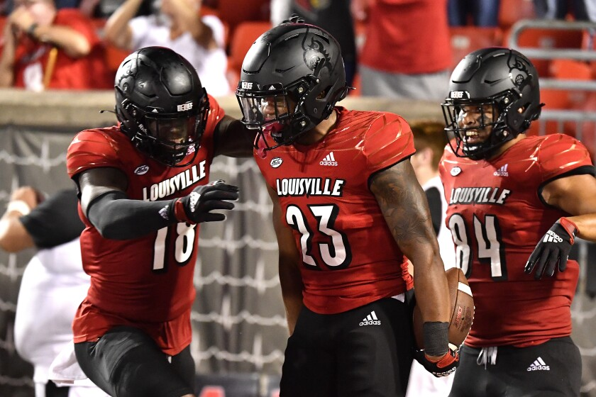 Louisville running back Trevion Cooley, middle, celebrates his 45-yard, fourth-quarter touchdown catch Sept. 17, 2021.