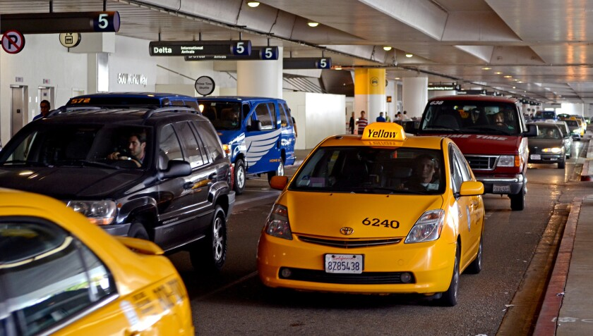 Taxi cabs and shuttles make their way through Los Angeles International Airport.