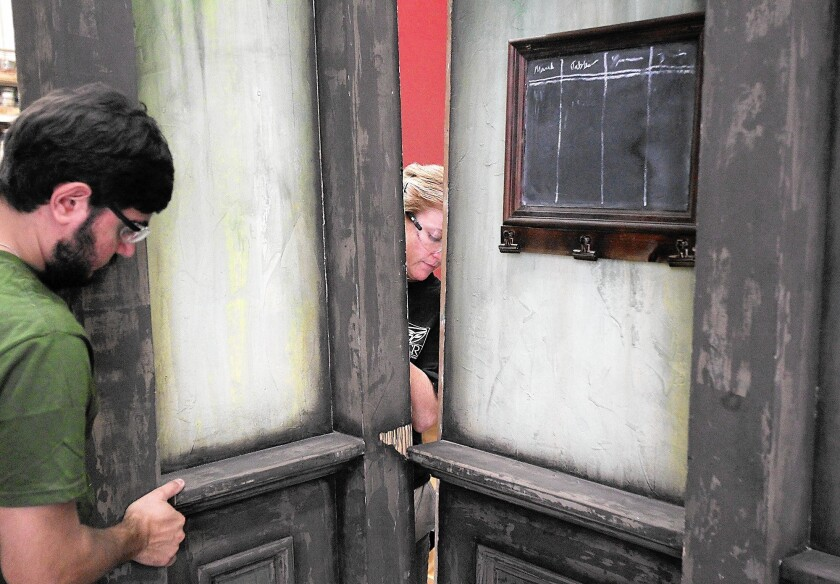 """Production crew members Derek Epstein, left, and Mandy Horak carefully fit a side panel into place for one of the backdrop scenes for """"A Christmas Carol."""" SCR's technical and scenic crews have reassembled the same stage set for """"A Christmas Carol"""" for more than 30 years."""
