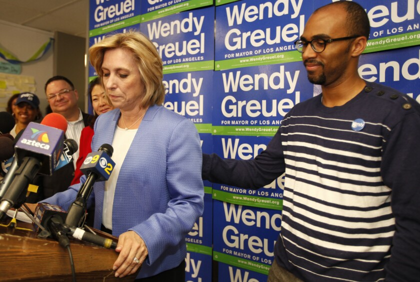 Wendy Greuel is consoled by supporter Todd Hawkins while addressing a press conference pledging her support to Eric Garcetti based on election results in the Los Angeles Mayoral campaign.